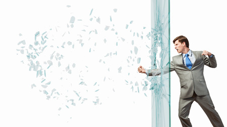 fedup: Furious businessman crashing glass wall with fist punch Stock Photo