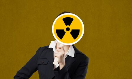 radiactividad: Unrecognizable businesswoman hiding her face behind radioactivity sign