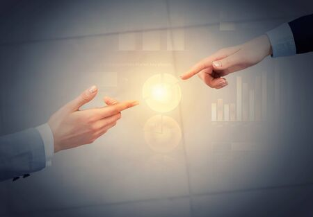 fingers on top: Top view of two businesswpeople reaching fingers to touch each other Stock Photo