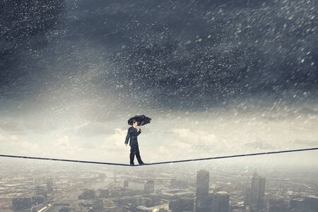business risk: Walking on rope businessman with black umbrella