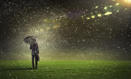 sotto la pioggia: Punto di vista posteriore di uomo d'affari con l'ombrello in piedi sotto la pioggia