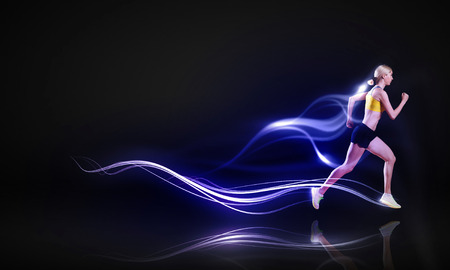 Young woman athlete running fast on dark