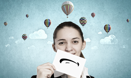 Young businesswoman holding paper with unhappy sad smiley Stock Photo