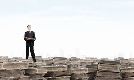 lawer: Young businesman standing on pile of old books