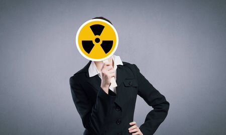 radiactividad: Unrecognizable businesswoman hiding her face behind radioactivity sign