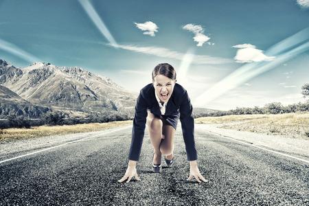 metas: Empresaria determinada joven de pie en posición de inicio