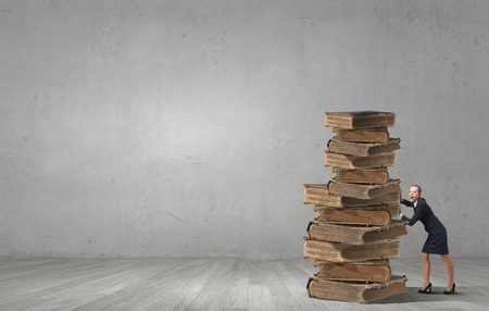 master degree: Young woman pushing huge pile of old books