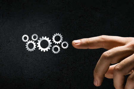 management team: Close up of hand and gears mechanism on black  Stock Photo