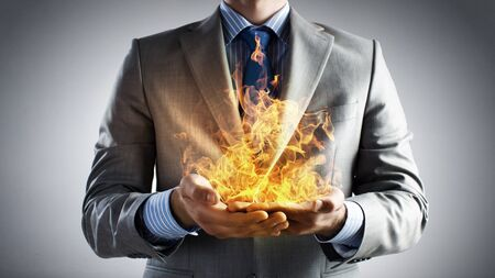 hands fire passion: Young businessman holding fire flames in palms