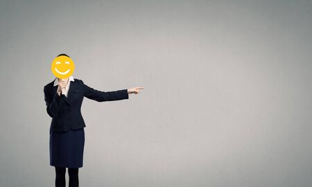 unrecognizable: Unrecognizable businesswoman hiding her face behind mask and showing direction