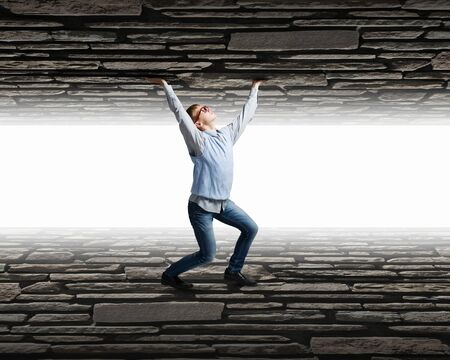 under pressure: Young man under pressure between two stone walls