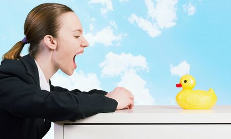 decoy: Young businesswoman screaming on yellow rubber duck toy