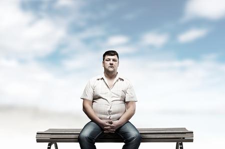 gordos: Hombre gordo sentado en el banco y mirando a puerta cerrada