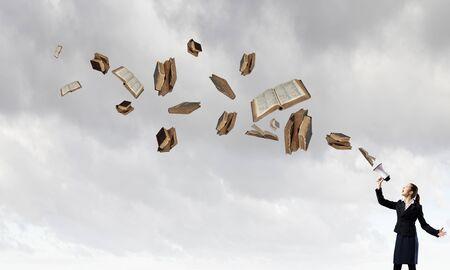 libros volando: Empresaria joven que grita en el meg�fono y los libros de volar Foto de archivo