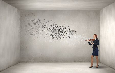 virtuoso: Young businesswoman in cement room playing violin Stock Photo