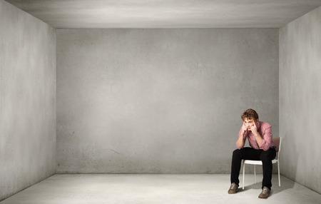 一人で椅子に座って意気消沈した男 写真素材