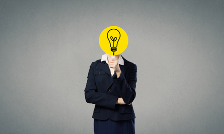 hidden success: Unrecognizable businesswoman hiding her face behind bulb shaped mask
