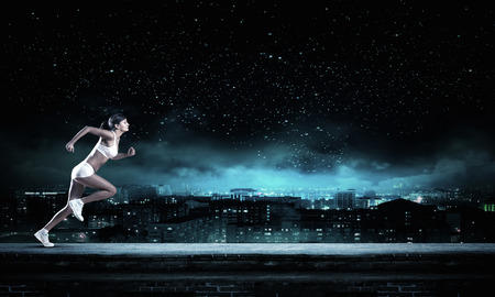 Young woman athlete running fast on dark background Stockfoto