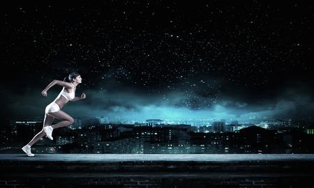 atleta: Mujer Joven atleta corriendo r�pido en fondo oscuro