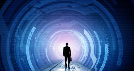 tecnologia: Vista traseira do homem de negócios com mala de viagem nas mãos olhando para o painel virtual