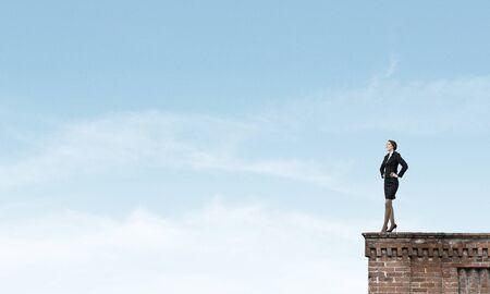 authoritative woman: Confident pretty businesswoman standing on building top