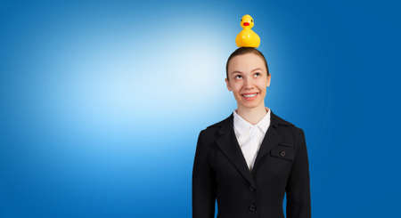 head toy: Young businesswoman and yellow rubber duck toy on head