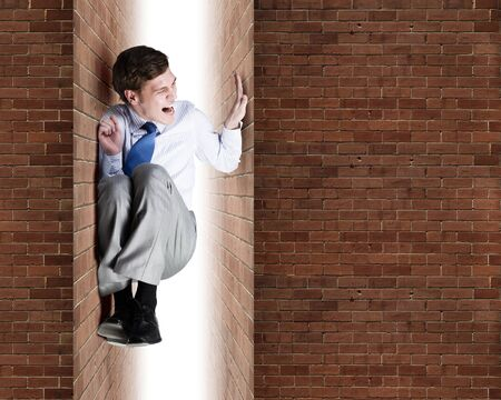 between: Young troubled businessman trapped between two walls