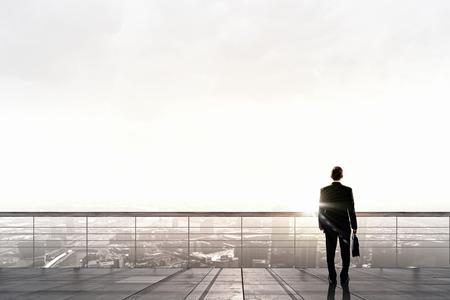 市を見て屋根の上に立っての実業家の背面図