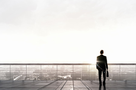Achter mening van zakenman die op het dak te kijken naar de stad