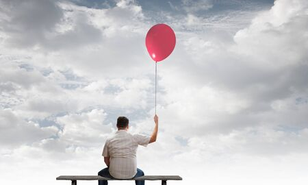 Fat man sitting on bench with his back with balloon in hand