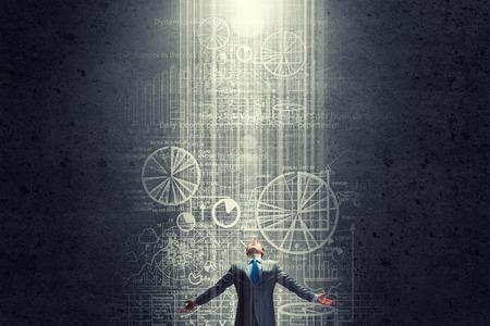 LIDER: Hombre de negocios con las manos apartadas de pie en la luz que viene de lo alto