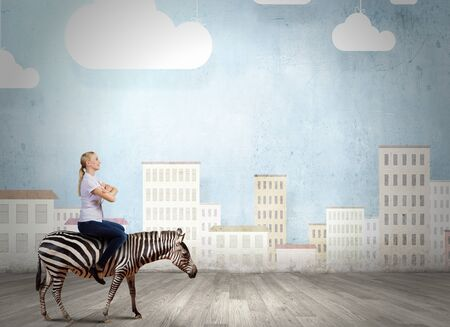 fearless: Young pretty fearless woman riding zebra animal Stock Photo