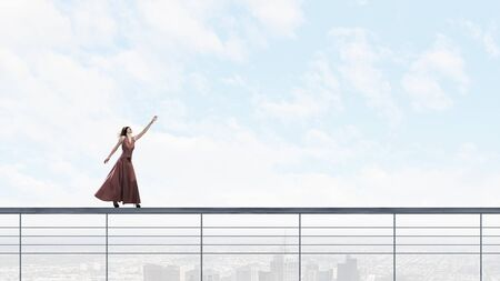 blindfold: Woman in evening dress and blindfold walking on parapet Stock Photo