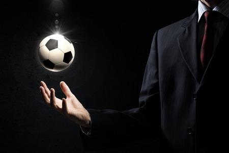 pelota de futbol: Primer plano de hombre de negocios elegante con balón de fútbol en la mano Foto de archivo