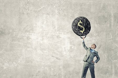 heavy weight: Young businessman lifts up heavy weight with dollar sign