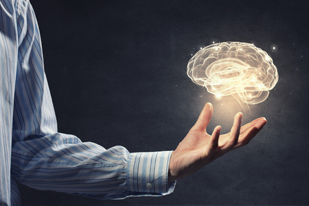 innovation: Close up of businessman holding digital image of brain in palm Stock Photo