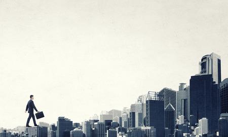exito: Joven empresario caminando en edificios techos que representan el concepto de éxito