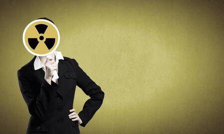 radioactivity: Empresaria irreconocible ocultando su rostro detrás de signo radiactividad Foto de archivo