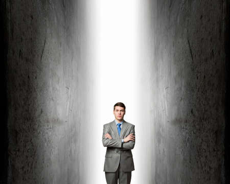 mani incrociate: Young confident businessman with hands crossed on chest between two walls