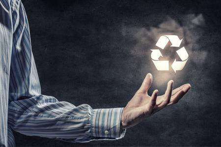reciclar: Empresario con signo de reciclaje en la mano