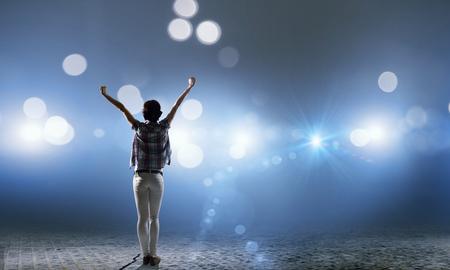 Vue arrière de la fille avec les mains debout dans les lumières de la scène Banque d'images
