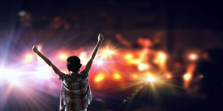 play acting: Back view of girl with hands up standing in stage lights