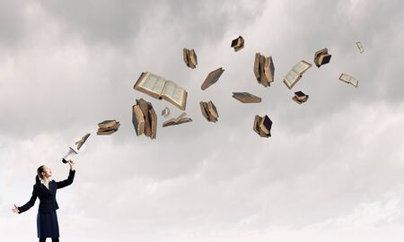 libros volando: Empresaria joven que grita en el megáfono y los libros de volar Foto de archivo