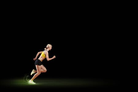 Young woman athlete running fast on dark background Stock Photo