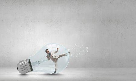 braking: Businessman inside light bulb braking it to get out