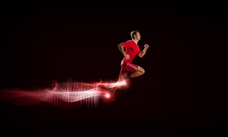 action sports: Running man in red sport wear on red background Stock Photo