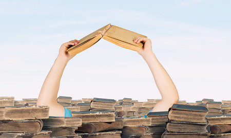 Hand with book reaching out from pile of old books Banco de Imagens