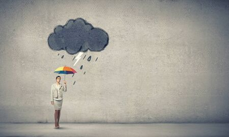 Young businesswoman with colorful umbrella under black cloud Stock Photo