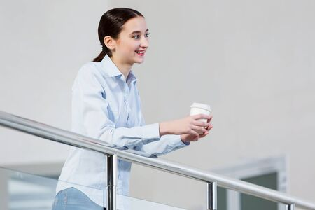 casual caucasian: Casual caucasian woman standing at balcony with coffee in hands