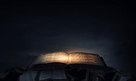 libros antiguos: Antiguo libro mágico negro con luces en las páginas Foto de archivo